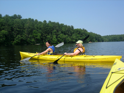 A host and student kayaking together